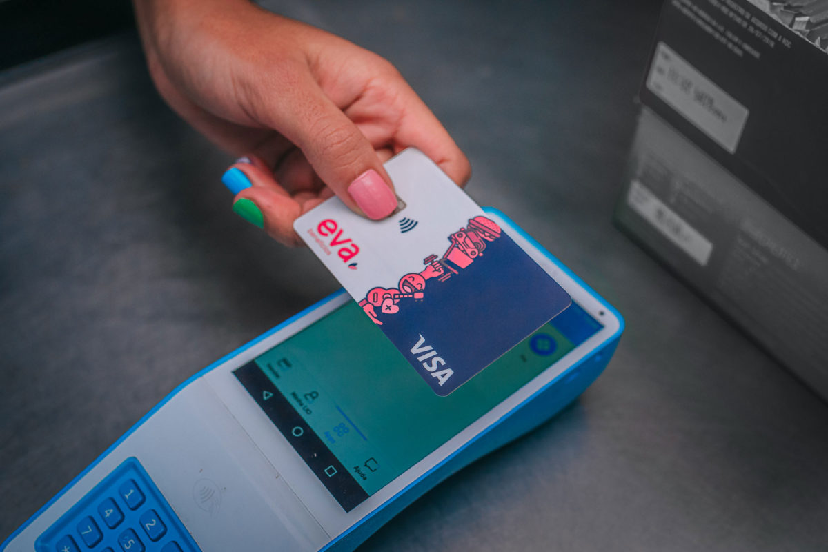 uma mão aproximando o cartão da Eva Benefícios numa máquina de cartão